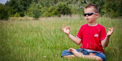 Child meditating in field